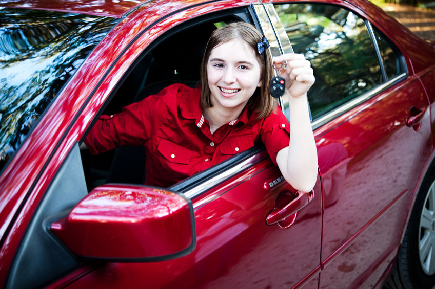 Teenage girl with her driver's license driving a new car and holding keys. Ways to prevent impaired teen driving