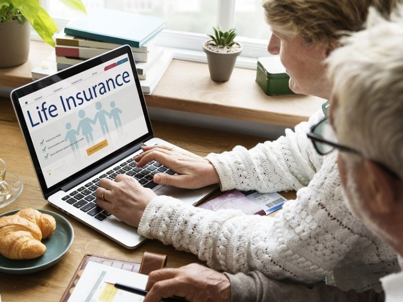 elderly couple reviewing life insurance policy online